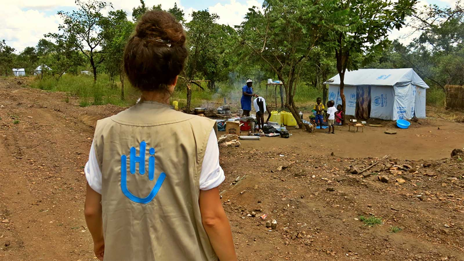 A-female-wearing-a-vest-with-the-Humanity- -Inclusion-logo-stands-across-from-a-family-at-a-refugee-camp-in-Uganda