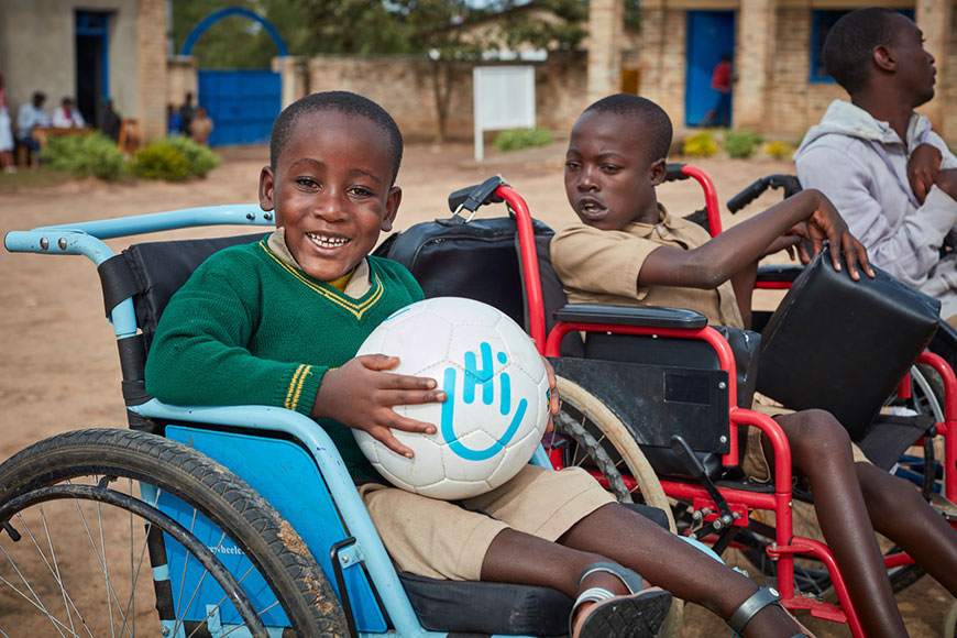 Jadot -6 -loves-to-go-to-school-and-dreams-of-becoming-a-doctor-some-day.-He-receives-support-from-HI's-team-in-Rwanda.-Jadot-sits-in-his-wheelchair-in-a-green-sweater -holding-an-HI-soccer-ball