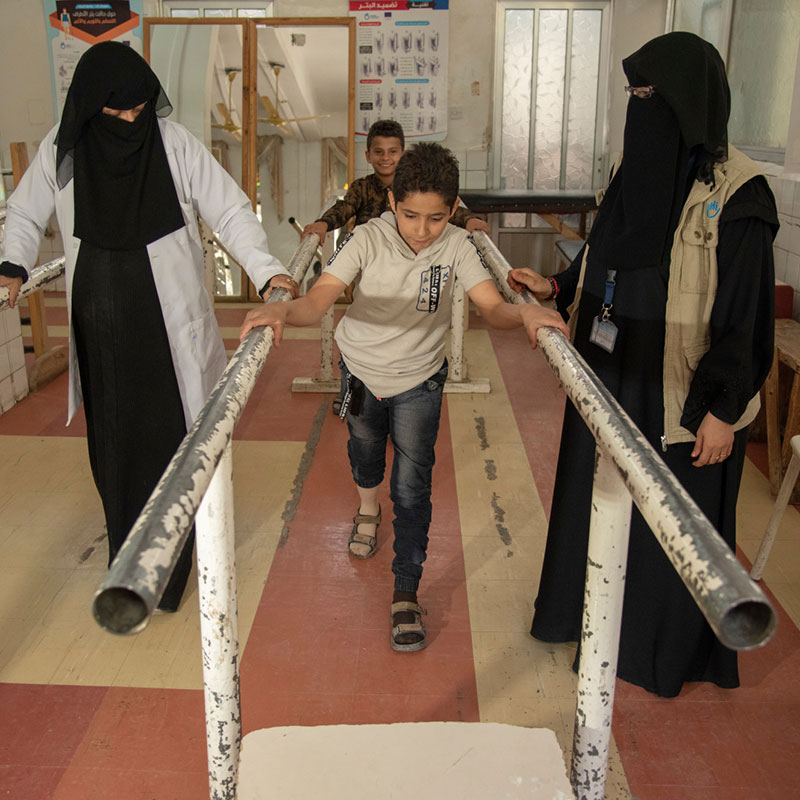 Yasser, who was injured in a bombing in Yemen, learns how to walk on his new prosthetic with support from HI physical therapists.