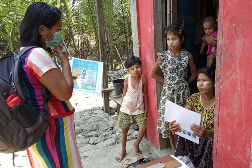 A Humanity & Inclusion staff member in Myanmar teaches teaches a Rohingya family how to stay safe from COVID-19.