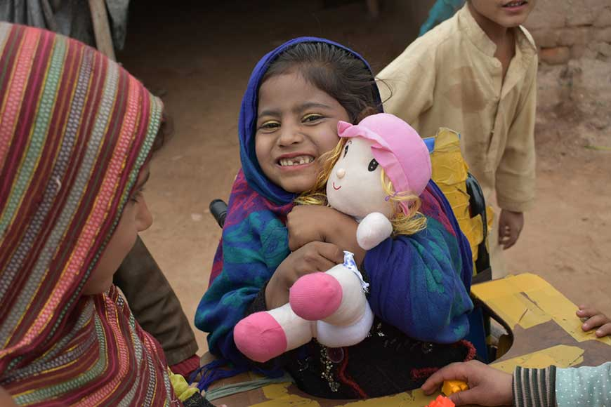 Samina smiles while holding a doll in her wheelchair in Pakistan.