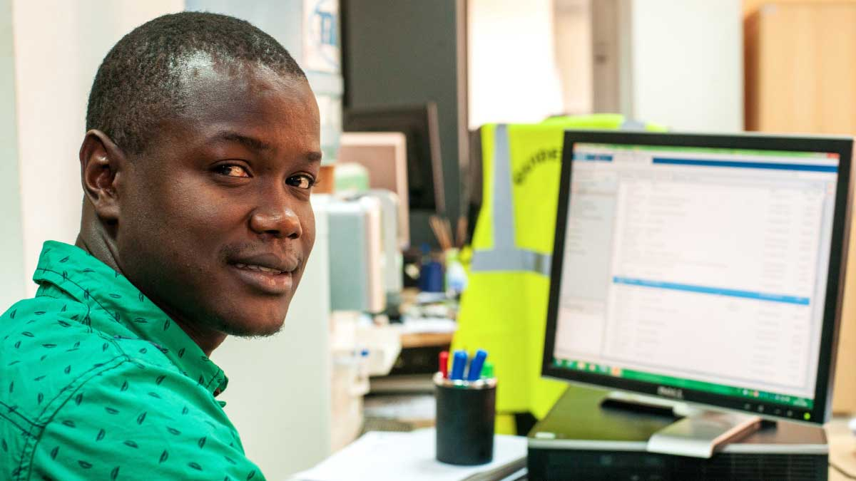 Mamadou-Bah -who-works-as-a-paid-intern-at-a-bank-in-Senegal -sits-in-front-of-his-desk
