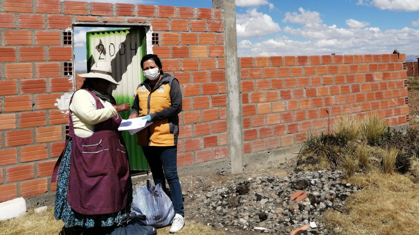 A masked worker distributes food in Bolivia.