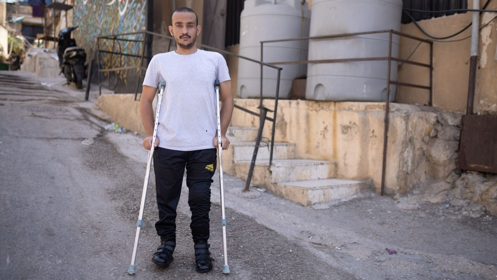 c_Tom-Nicholson_HI__A_man_stands_with_crutches_and_special_boots_in_an_alleyway_in_Lebanon.jpg