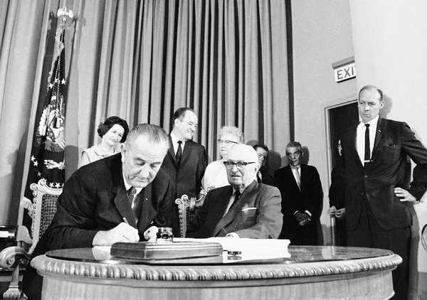 President Johnson signs Medicare into law.