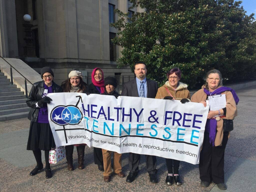 Group of Healthy and Free Tennessee supporters holding a banner of Healthy and Free Tennessee's logo pictured with a legislator