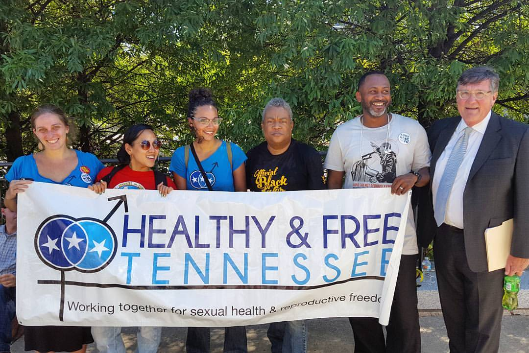Group of multi-racial healthy and Free Tennessee supporters hold banner with Healthy and Free Tennessee logo pictured with legislator
