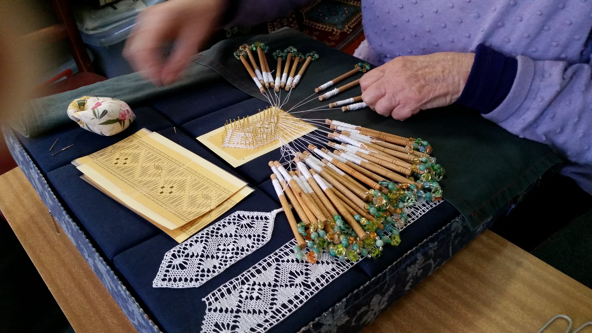 Making lace with bobbins and thread