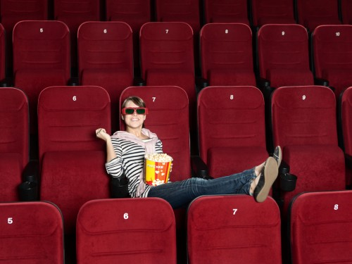 woman smiling, sitting by herself in an empty movie theater