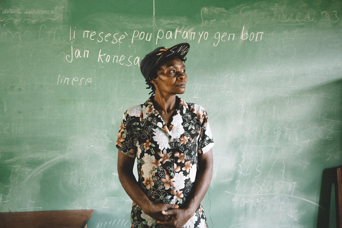 A student in a Adult Literacy Class stands in front of her work at the chalkboard of a school built by In a Perfect World.