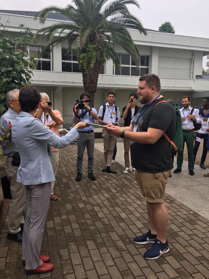 Leder i Røde Kors Ungdom, Robert Flobergseter, foran en skolen som ble bombet. Her mottar han historien til en av de to elevene som overlevde bombingen.