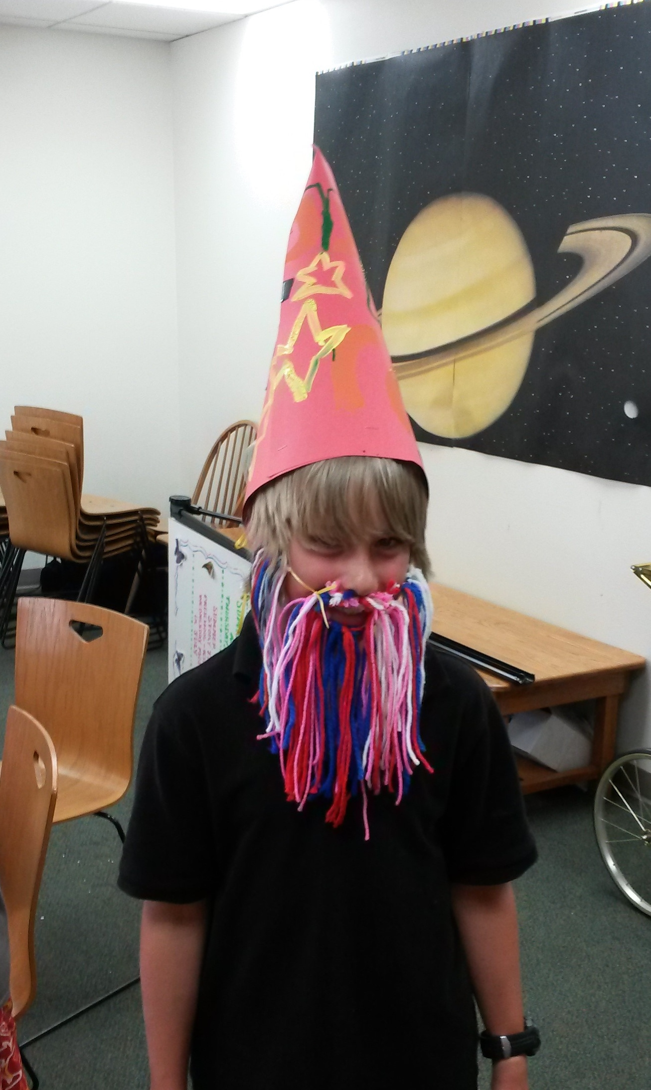 Child wearing cone hat and yarn beard