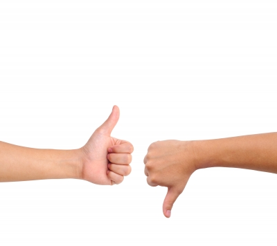 Thumbs up and thumbs down indicating conflicting opinions