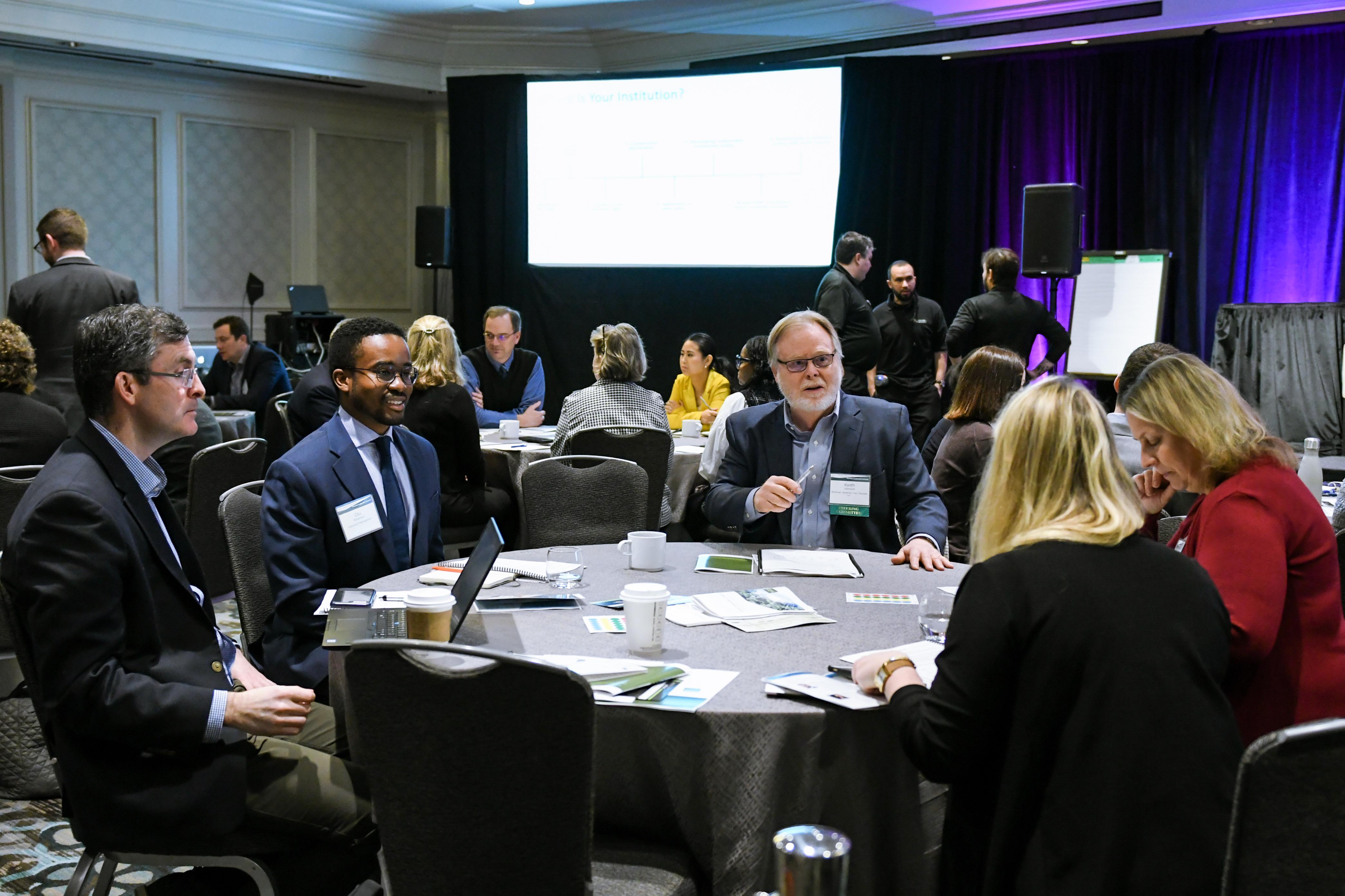 participants discuss investing topics at a table