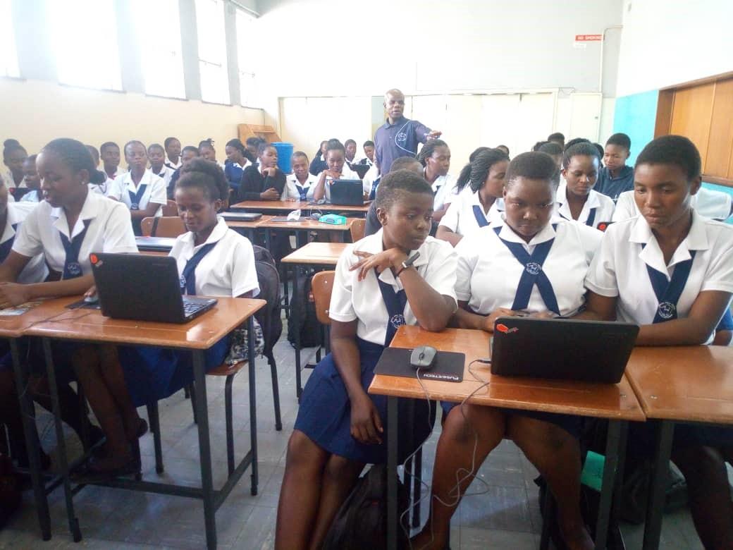 Female schoolchildren crowd around laptops in a classroom