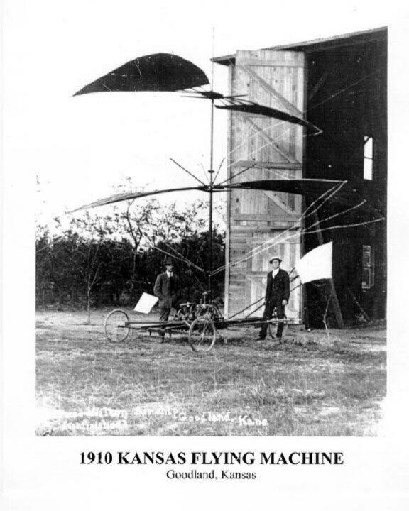 Two men standing in front of the first patented helicopter.