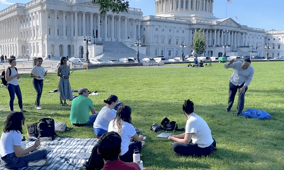 Group gathered on grass in front of the U.S. Capitol. Some people are sitting, and a few are standing. In front of the group, Rabbi Jason Kimmelman-Block leads  Sukkot ritual of beating a willow branch against the ground to let go of destructive, white supremacist ideas so we can build a country where everyone thrive.