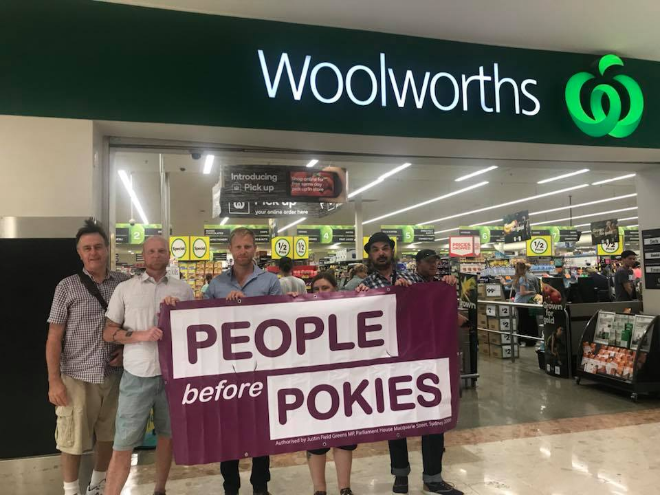 Banner reading People before Pokies outside of a Woolworths store