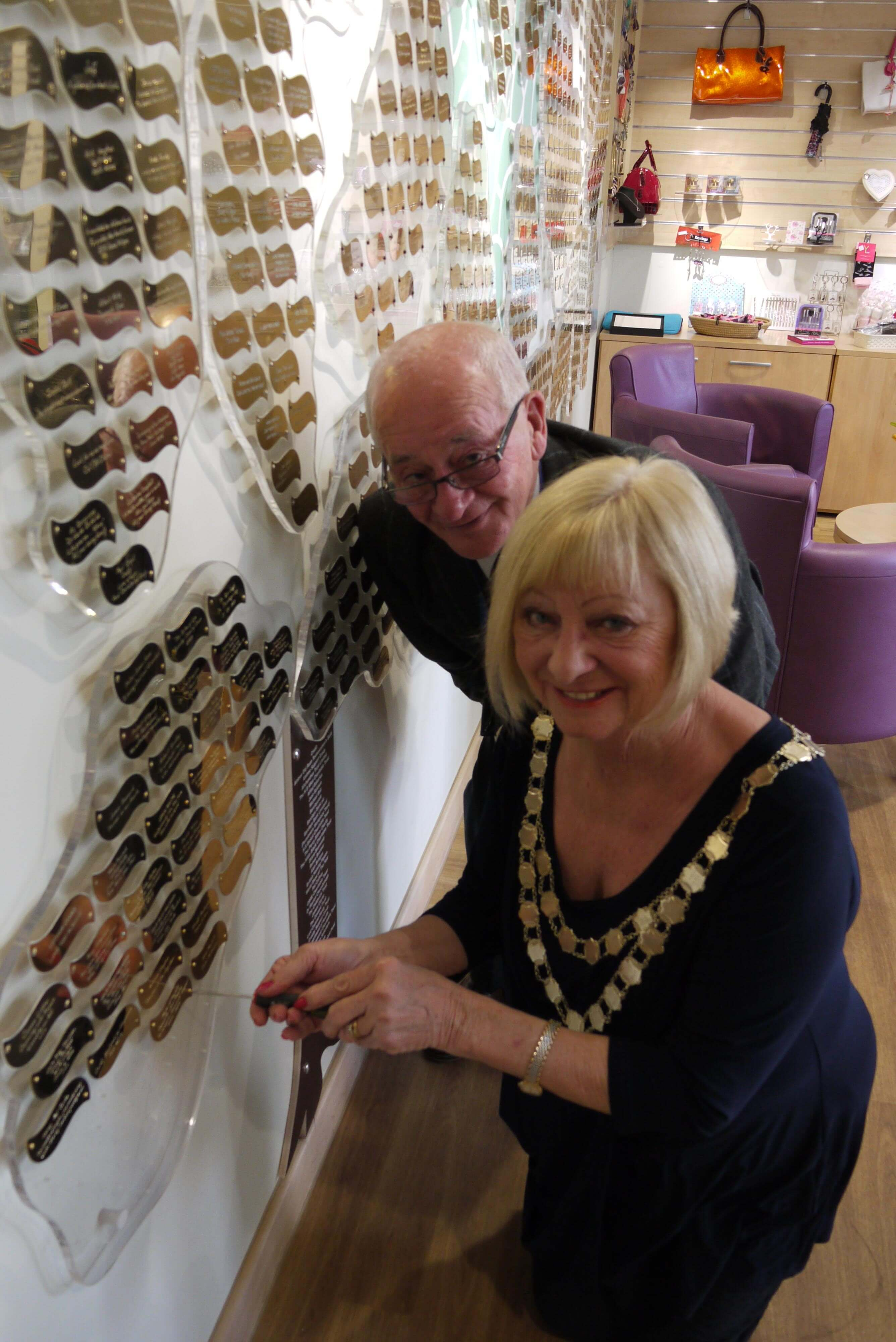 Mayor of Maghull Cllr Joan Deegan and consort Cllr Rod Deegan add a golden leaf to Woodland's Hospice fundraising tree after raising nearly £10,000 for the charity.