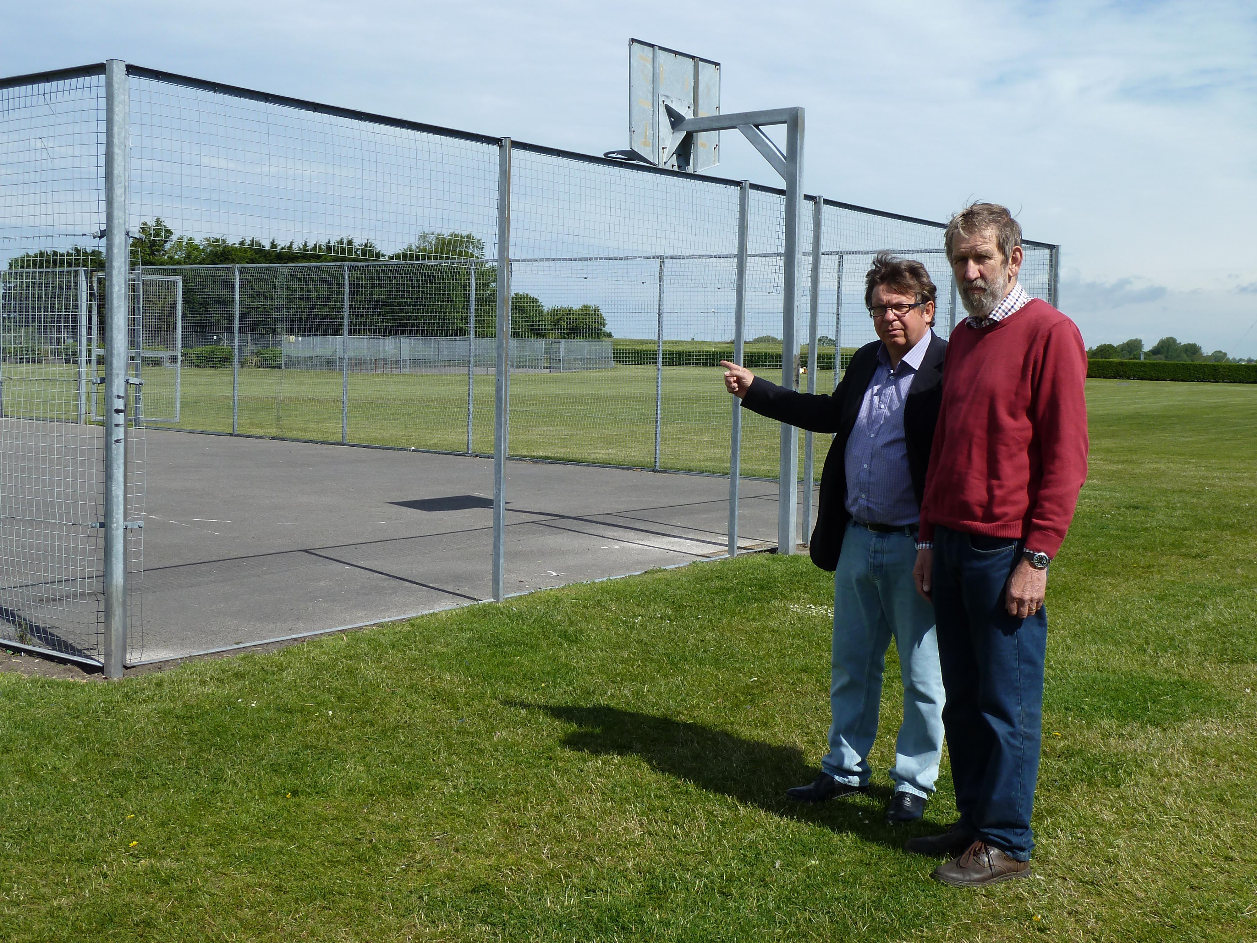 Lydiate Parish Council chairman Cllr John Bailey and vice chairman Cllr Andy Wilson at the Sandy Lane basketball court where sections of the fencing was also stolen