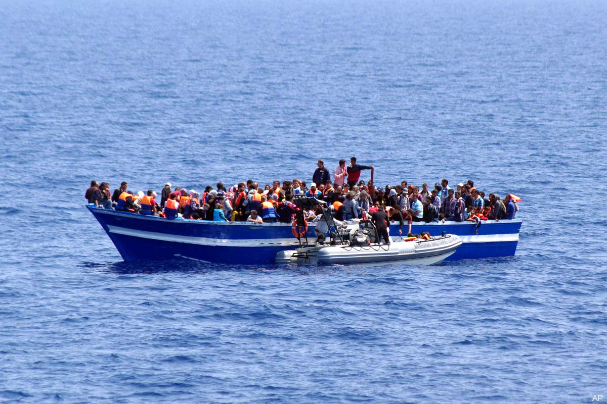 italian-navy-a-boat-filled-with-migrants-receives-aid-from-an-Italian-Navy-motor-boat.jpg