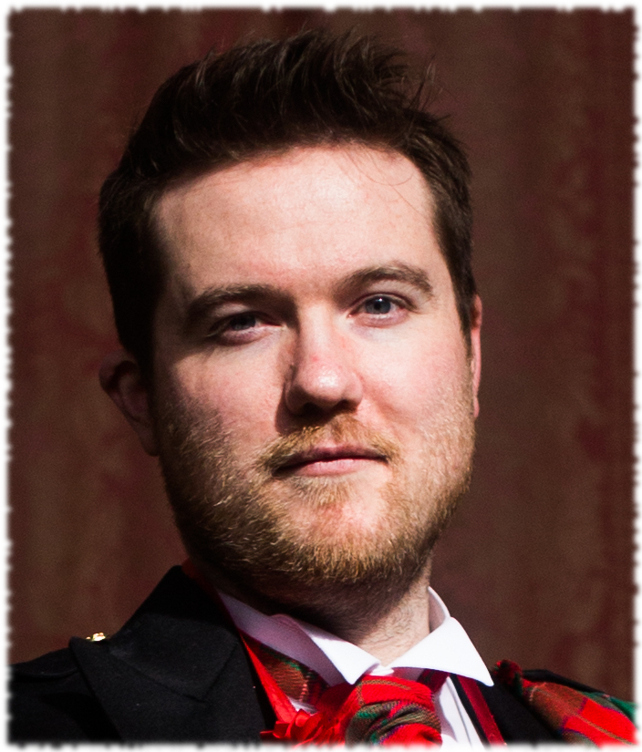 Alex Thomas has short dark hair and a light beard. He is wearing a red tartan scarf with a black jacket.