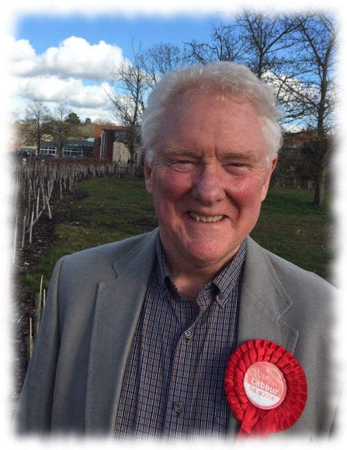 Mike is standing in front of a glorious blue sky. He's smiling; he is wearing a red Labour rosette.