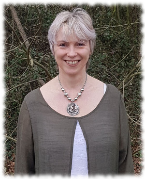Jacqui is smiling; she is wearing a silver cardigan with a rose necklace.