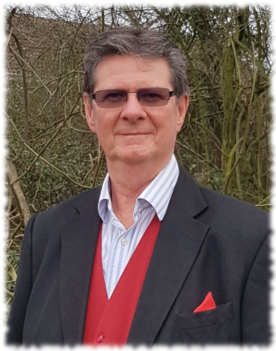 Verd has dark hair and smoked glasses. He is wearing a navy jacket over a red waistcoat.