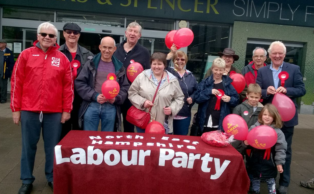 A crowd of people including children stand outside a supermarket. They are behind a table draped with a red banner reading 'North East Hampshire Labour Party'. They are holding red balloons and are smiling.