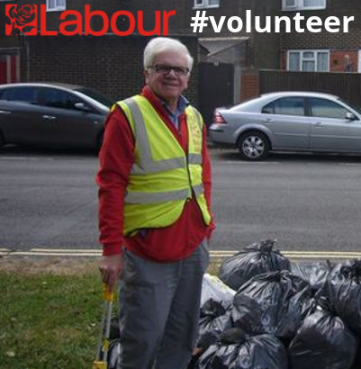 Barry Jones; a smiling man with glasses. He's wearing a yellow hi-vis vest with the red Labour rose logo, and holding a litter-picker.