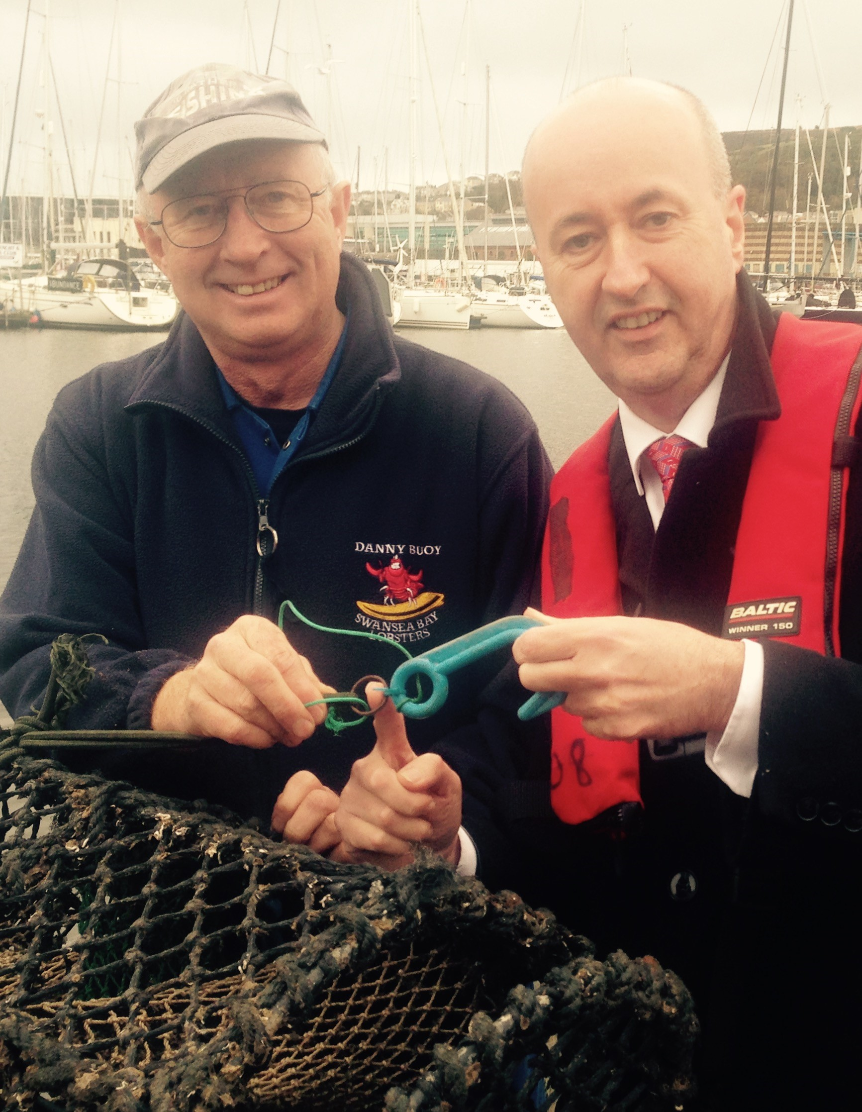 Skipper of Danny Buoy Nigel Sanders shows Geraint Davies MP lobster pot that becomes safe after loss
