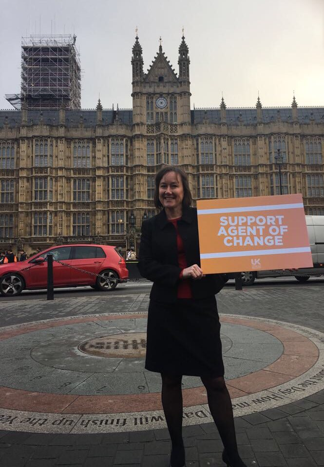 Jo Stevens MP holding a 'support agent of change' campaign placard