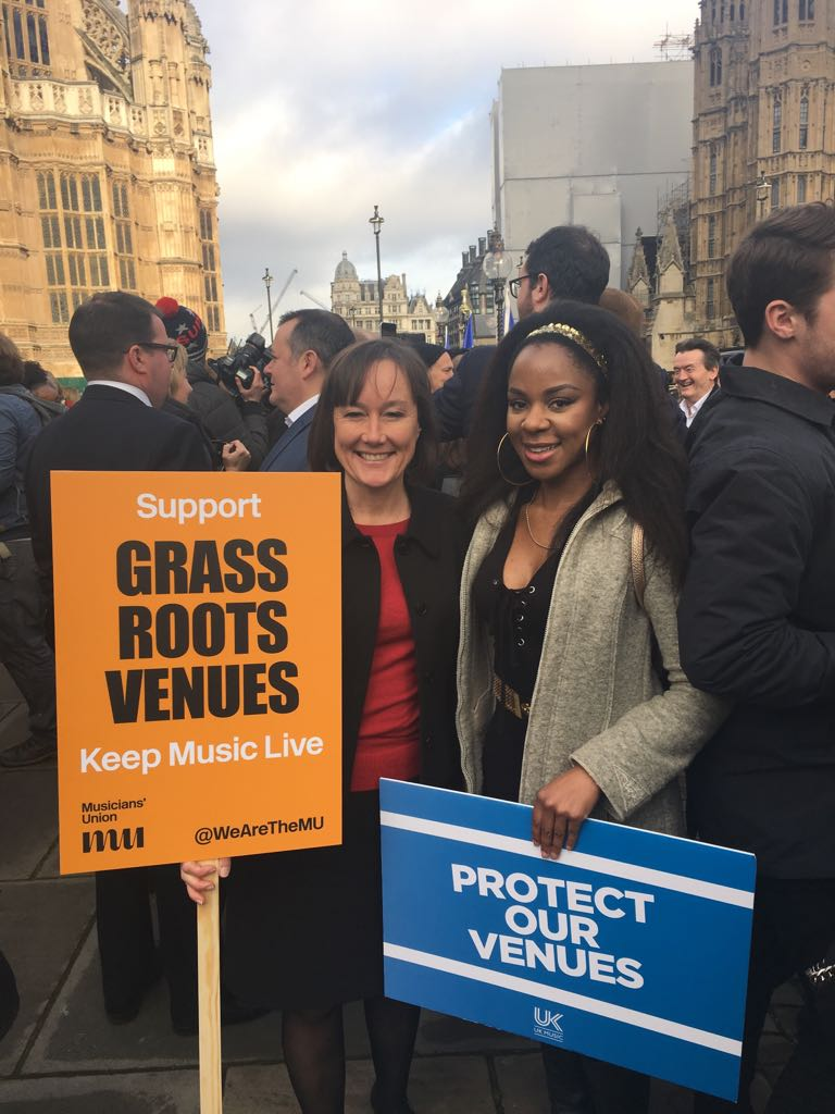 Jo Stevens MP and musician Ninja holding campaign placards
