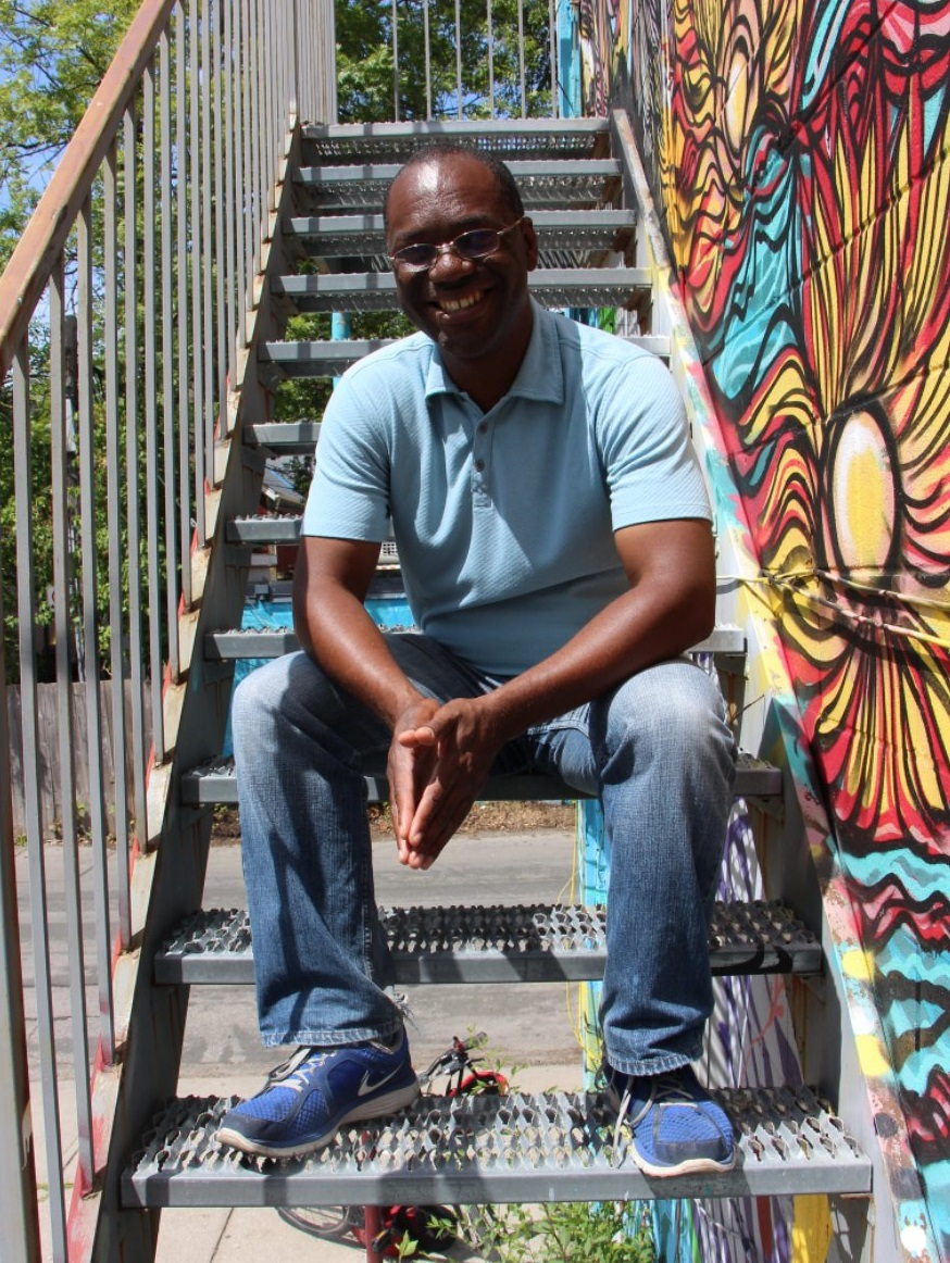 Lanrick Bennett Jr. sitting on alleyway stairs, colourful mural on the wall next to him.