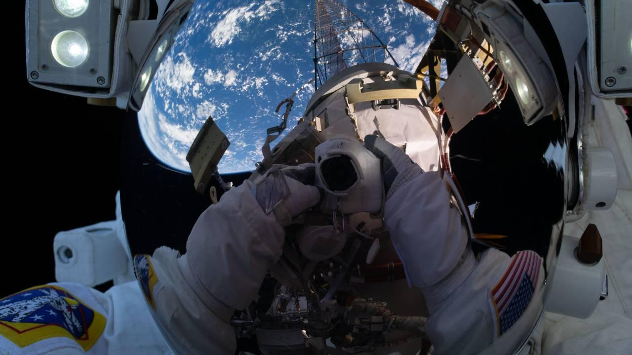 """NASA astronaut Michael Hopkins points his cameratoward his spacesuit helmet's reflective shield and takes an out-of-this-world """"space-selfie"""" during a spacewalk he conducted with fellow NASA astronaut Victor Glover. NASA Feb 1, 2021"""