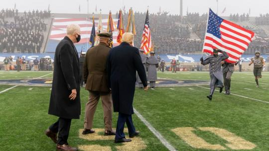 President Donald J. Trump is escorted on to the football field as an Army cadet runs with a U.S. flag Saturday, Dec. 12, 2020, prior the coin toss to the start of the 121st Army-Navy football game at the U.S. Military Academy at West Point, N.Y.