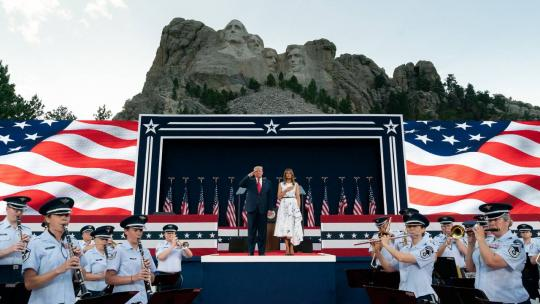 President Trump salutes and First Lady Melania Trump places her hand on her heart as the US Air Force Academy Concert Band performs the National Anthem during a Fourth of July celebration Friday, July 3, 2020, at Mount Rushmore National Memorial.