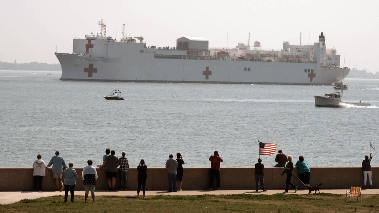 NORFOLK (March 28, 2020) People gather to watch the Military Sealift Command hospital ship USNS Comfort (T-AH 20) depart Naval Station Norfolk, Va., March 28, 2020. (US Navy photo by Mass Communication Specialist 1st Class Joshua D. Sheppard/Released)