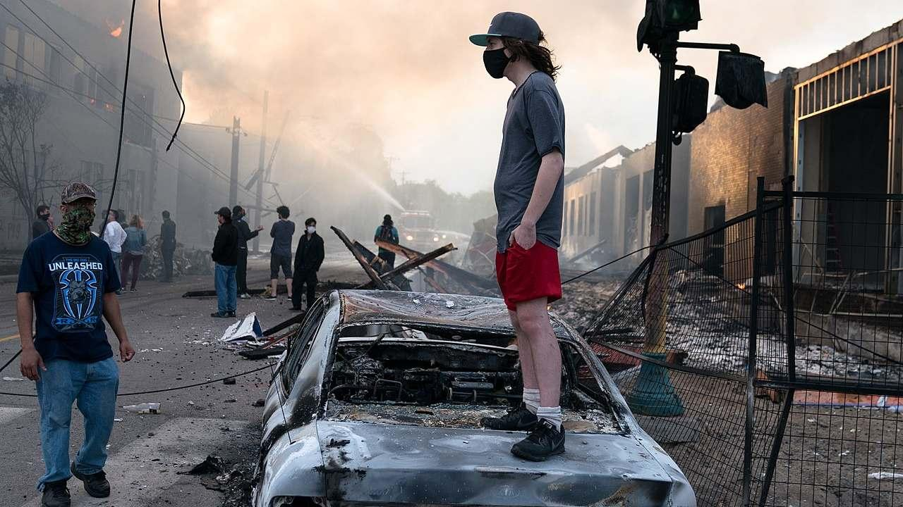 A man stands on a burned out car on Thursday morning as fires burn behind him in the Lake St area of Minneapolis, Minnesota. May 28, 2020 (Lorie Shaull/Flickr/CC BY-SA 2.0)