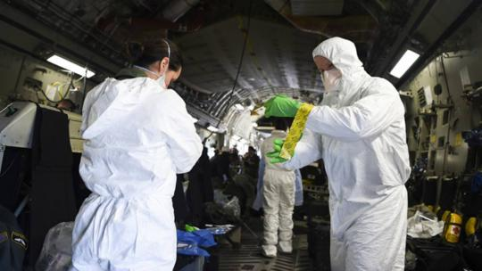 Airmen assist one another in donning their protective equipment. Engineered & implemented after the Ebola virus in 2014, the C-17 Globemaster III transportation isolation system is an enclosure the DoD can use to safely transport patients with COVID-19.