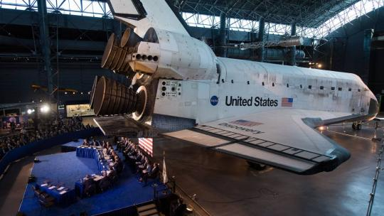 Members of the National Space Council are seen under space shuttle Discovery during the council's sixth meeting, Tuesday, Aug. 20, 2019 at the Smithsonian National Air and Space Museum's Steven F. Udvar-Hazy Center in Chantilly, Va.