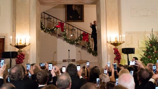 President Donald J. Trump waves as he and Mrs. Trump walk down the Grand Staircase to greet guests at the Congressional Ball Saturday, Dec. 15, 2018, in the Grand Foyer of the White House. (Official White House Photo by Andrea Hanks)