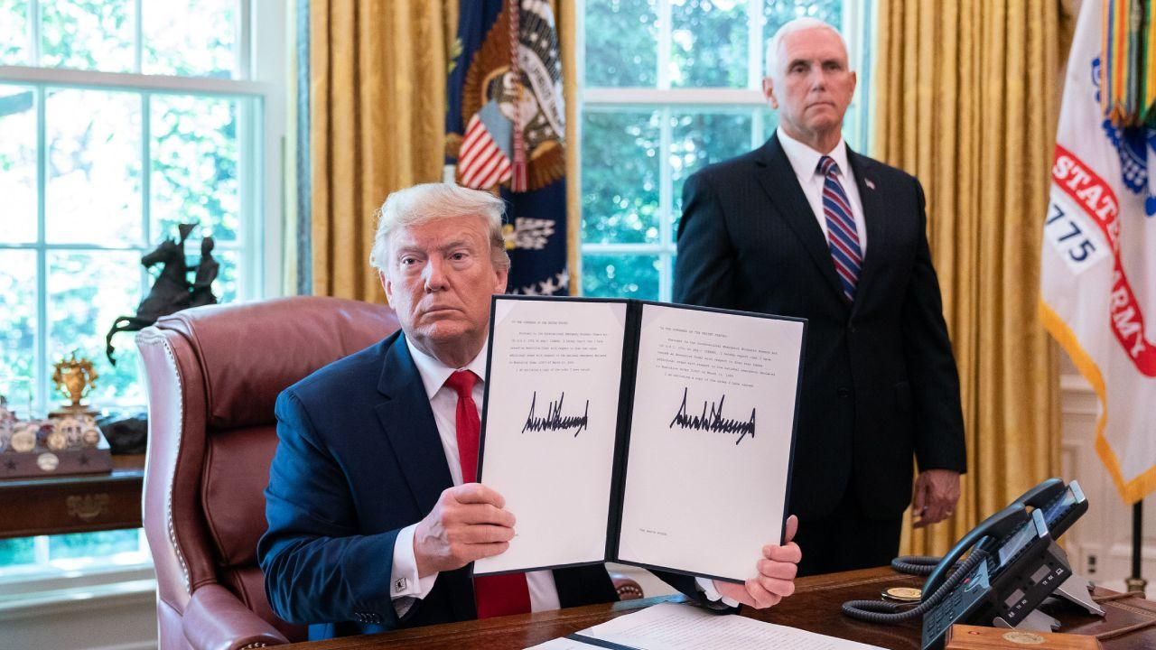 President Donald J. Trump displays his signature on an Executive Order to place further sanctions on Iran Monday, June 24, 2019, in the Oval Office of the White House. (Official White House Photo by Joyce N. Boghosian)