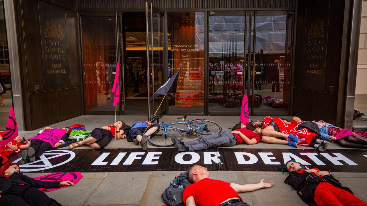 """Seen here, an XR (Extinction Rebellion) """"Die-In"""" in front of the Royal Opera House in London England. July 2, 2019. (Photo: Anthony Jarman)"""