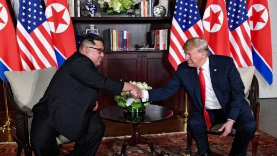 Presidents Trump and Kim shaking hands in the summit room during the 2018 Singapore Summit. June, 2018