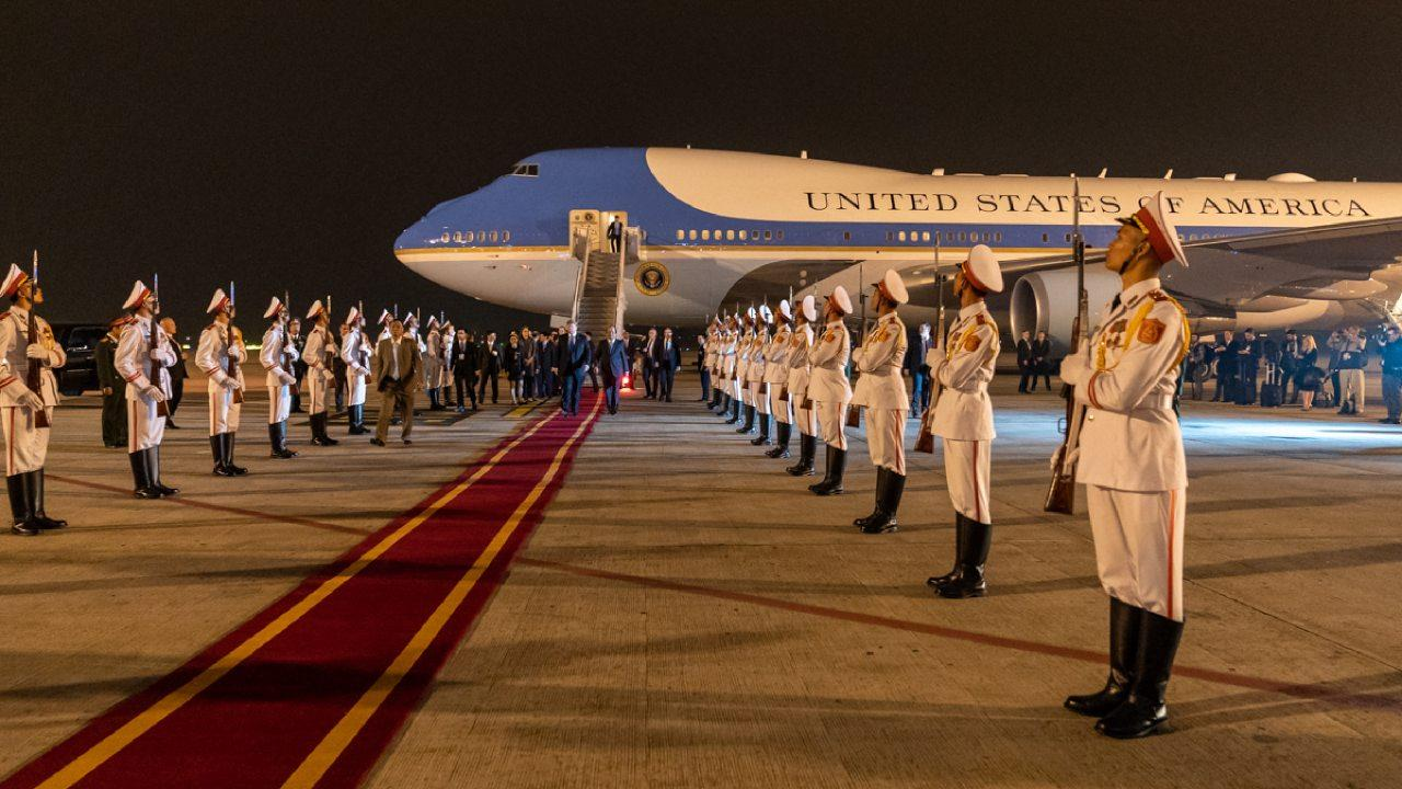 President Donald J. Trump, escorted by Mai Phuoc Dung, Director General of State Protocol of the Socialist Republic of Vietnam, walks along a red carpet from Air Force One and reviews an Honor Cordon upon his arrival Tuesday, Feb. 26, 2019, in Hanoi.