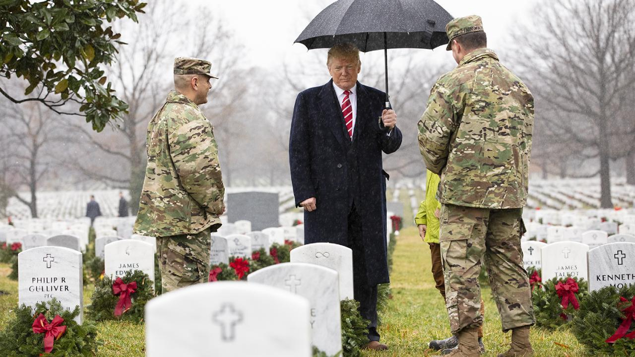 President Donald J. Trump walks through Arlington National Cemetery's Section 60 with Army National Military Cemeteries and Arlington National Cemetery leadership Saturday, Dec. 15, 2018, during the annual Wreaths Across America event in Washington, D.C.