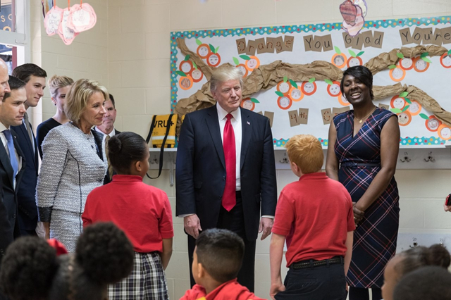 President Trump and Secretary of Education Betsy DeVos visit Saint Andrew's Catholic School in Orlando, Florida, March 3, 2017. By the White House from Washington, DC - President Trump's First 100 Days: 24, Public Domain.