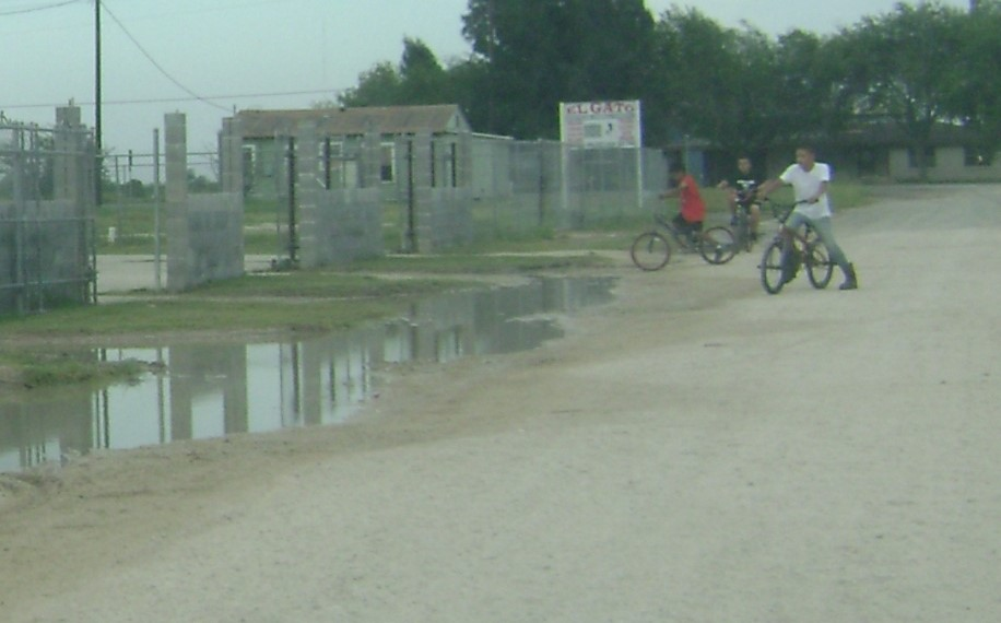 Water stagnates in colonia while children play nearby.